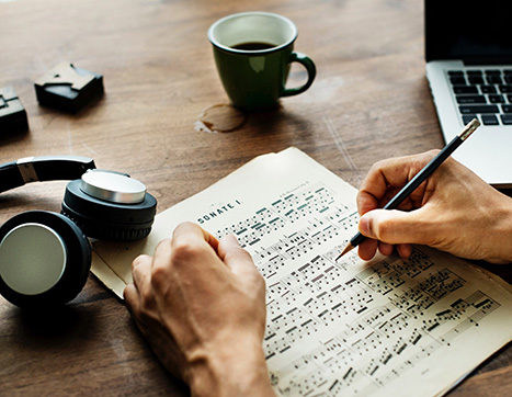 Composer working on sheet music at desk